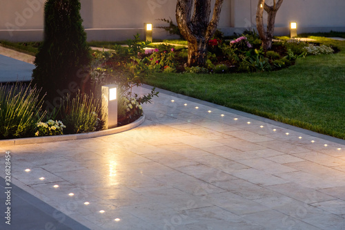 Obraz marble tile playground in the night backyard of mansion with flowerbeds and lawn with ground lamp and lighting in the warm light at dusk in the evening. - fototapety do salonu