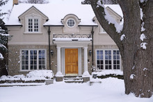 Snow Covered Stucco And Stone House With Large Tree In Front Yard