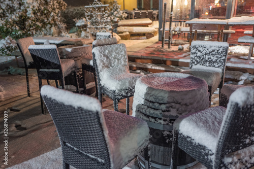 Платно tables and chairs in a cafe, snow covered