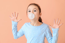 Cute Little Girl With Chewing Gum On Color Background