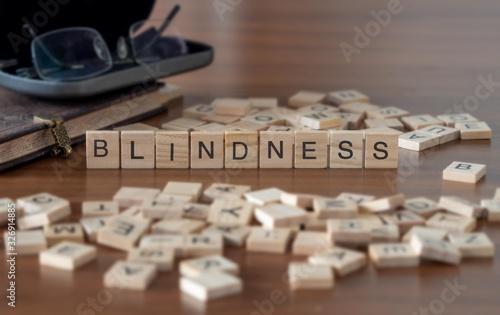 blindness concept represented by wooden letter tiles on a wooden table with glas Wallpaper Mural