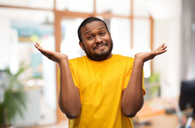 Expressions And People Concept - Clueless Young African American Man In Yellow T-shirt Shrugging Over Office Background