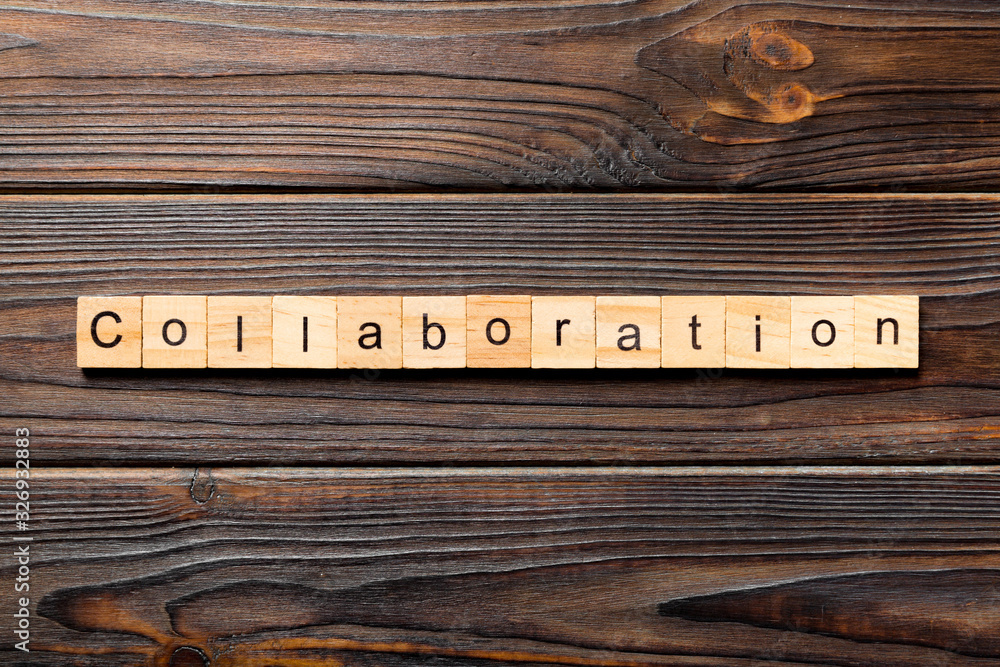 Fototapeta Collaboration word written on wood block. Collaboration text on wooden table for your desing, concept