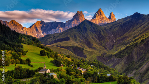 church in a village in the french alps with mountains 3000 meters high. Green meadows in spring