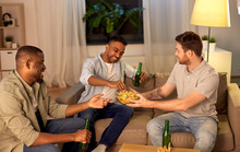 Friendship, Leisure And People Concept - Male Friends Drinking Beer And Eating Crisps At Home At Night