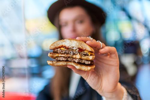 Fototapeta Woman eating burger bun with beef in fast food restaurant