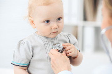 Doctor and patient in hospital. Little girl dressed in grey dress is being examined by doctor with stethoscope. Medicine concept