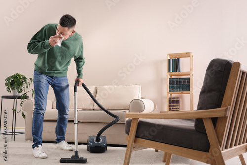 Obraz Man with dust allergy cleaning his home - fototapety do salonu