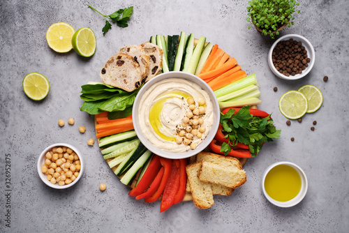 Fototapeta Hummus plate with a variety of vegetables and bread. Healthy snack or meze obraz