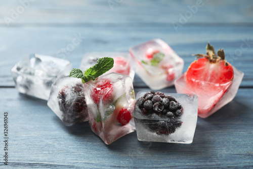 Fototapeta Ice cubes with different berries and mint on blue wooden table, closeup obraz