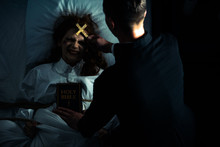 Exorcist With Bible And Cross Standing Over Demonic Obsessed Girl In Bed