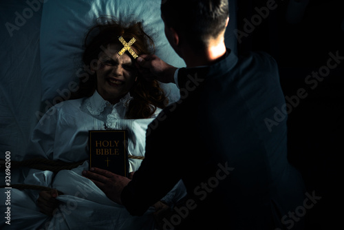 Fotografie, Tablou exorcist with bible and cross standing over demonic obsessed girl in bed
