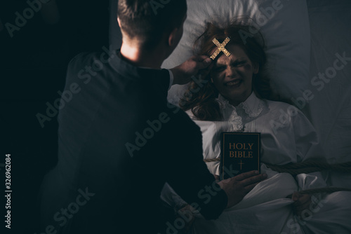 exorcist with bible and cross standing over demonic obsessed girl in bed Wallpaper Mural