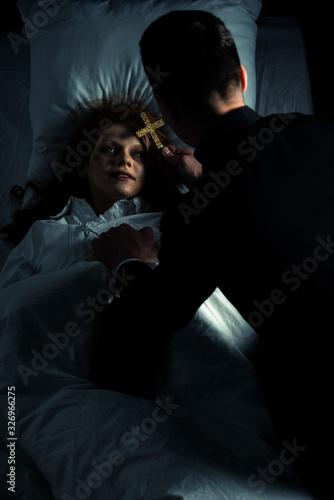 Fototapeta exorcist holding cross over female creepy demon in bed