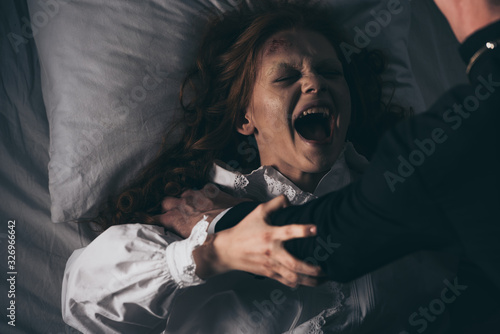 Photo exorcist holding yelling female demon in bed