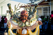 Person In Bright Demon Costume Poses For Photo On City Street At Dominican Carnival
