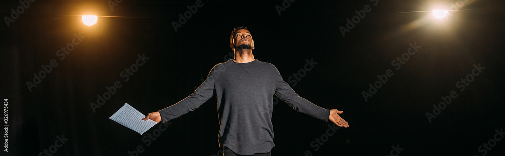 Fototapeta panoramic shot of african american actor holding scenario and standing on stage during rehearse