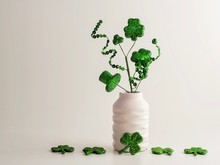 St. Patrick's Day Green Glitter Shamrock, Four Leaf Clover, Hat And Swirls In A White Vase With More Four Leaf Clovers Lined Up On A White Background.  Holiday Decoration For The Irish Holiday!