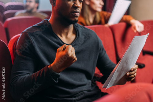 Fototapeta multicultural angry actor and actresses reading scripts in theater