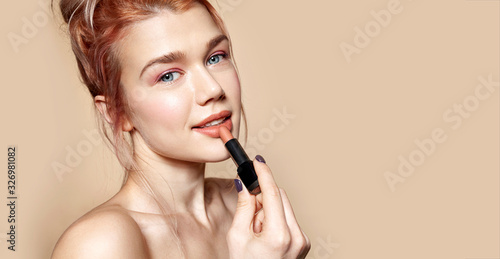 Portrait of gorgeous smiling woman holding rosy lipstick in hand Fototapet