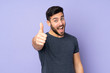 Leinwandbild Motiv Caucasian handsome man with thumbs up because something good has happened over isolated purple background