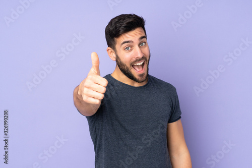 Caucasian handsome man with thumbs up because something good has happened over isolated purple background