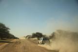 Fototapeta Sawanna - samochód terenowy mknący po szutrowej drodze afrykańskiej sawanny zostawiający za sobą chmurę kurzu