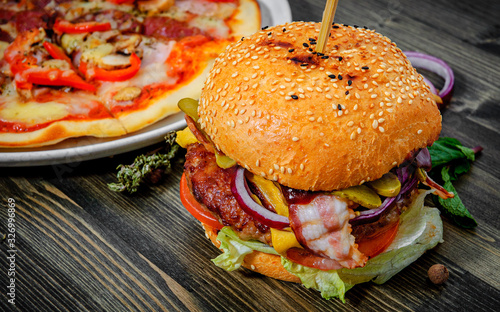bacon cheese burger with beef patty tomato onion and pizza on a wooden table © pavel siamionov