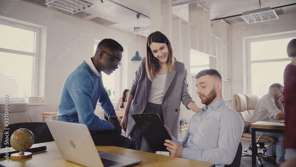 Fototapeta Caucasian female boss helping young multiethnic colleagues. Woman manager motivates employees in modern loft office 4K.