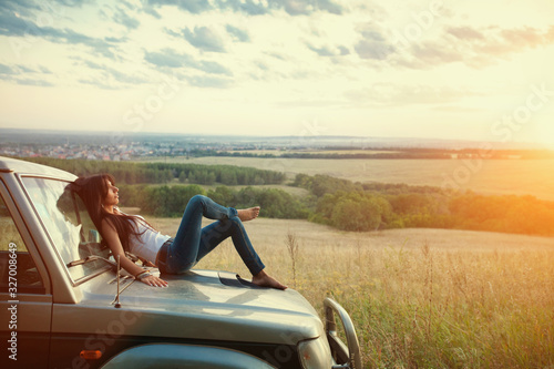 Fototapeta Attractive yong woman is lying on the car's hood and looking at sunset. Rural evening background. obraz