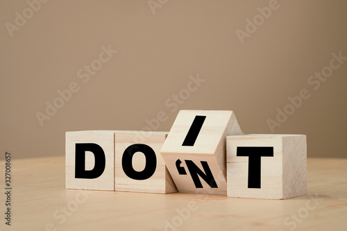 Photo Hand flipping wooden cubes for change don't to Do it