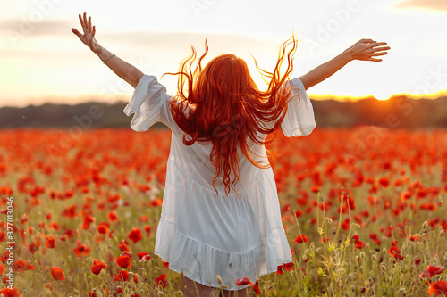 Fotomural Happy redhead smiling woman in white dress on field of poppies at summer sunset