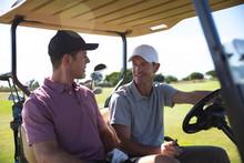 Golfers Sitting In Golf Buggy