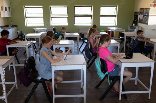 Group of schoolchildren sitting at desks using personal computers