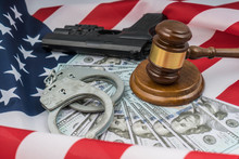 Judge Gavel, Handcuffs, Money And A Gun. American Flag Background Usa. Court Law, Crime And Punishment