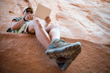 Hiker Resting Outdoors On Rock Ledge Using Digital Tablet