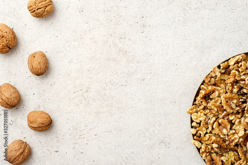 Vászonkép Whole and cracked walnuts, copy space in the middle on grey background