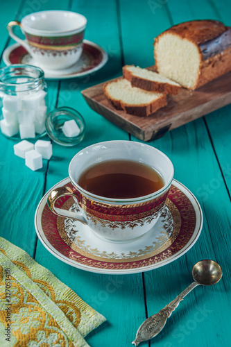 A tiffany color wooden table with a sliced cake on the cutting board, sugar cubes and two porcelain cups of tea Wallpaper Mural
