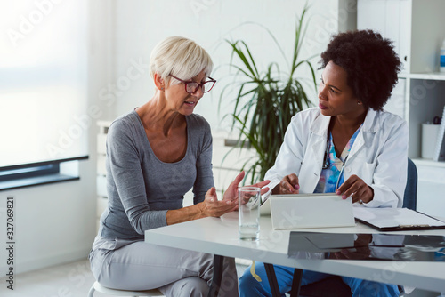 Cuadros en Lienzo A female doctor sits at her desk and chats to an elderly female patient while lo