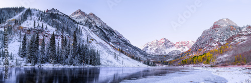 Maroon Bells morning sunrise panorama with sunlight on peak in Aspen, Colorado rocky mountain and autumn yellow foliage panoramic view winter snow