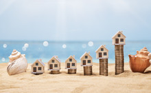 House Models Arranged On Stacked Coins At Beach