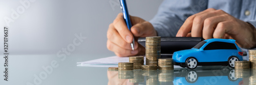 Fotomural Toy Car In Front Of Businessman Calculating Loan