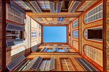 Looking Up View Of Sky At Enclosed By Residential Apartment Medieval Building Decorated Walls Courtyard With Colorful Windows And Opened Shutters In Siena, Tuscany, Italy