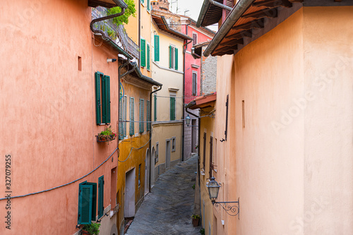 High angle aerial view on Chiusi, Italy street narrow alley in small historic town village in Umbria on sunny day with orange yellow bright vibrant colorful walls, windows shutters
