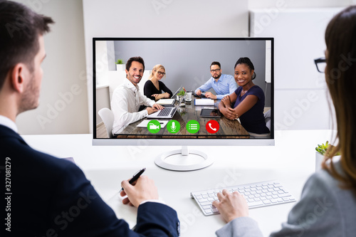 Two Businesspeople Video Conferencing On Computer - 327081279