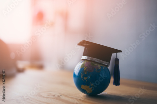 Obraz Education study abroad in Global world,Back to School and Graduation cap on student hand holding Earth globe map,Success of Global business study abroad educational,congratulation Graduation Ceremony - fototapety do salonu