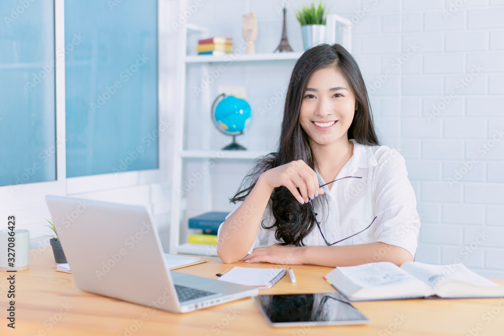 Fototapeta Education study abroad, Overseas Asian student girl sitting at table looking book while do homework by laptop making video call abroad to internet friend connection, happy mood smile broadly  library
