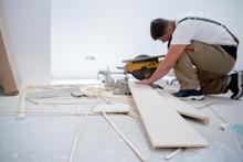 Man Cutting Laminate Floor Plank With Electrical Circular Saw