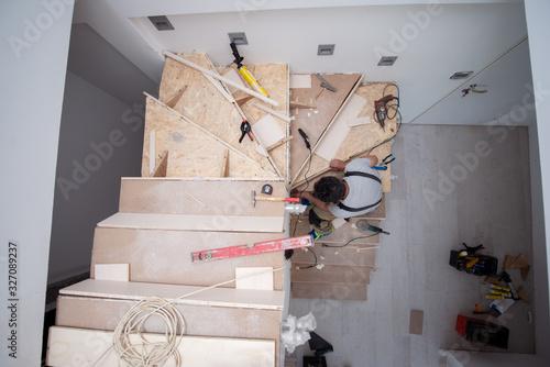 Photo carpenter installing wooden stairs