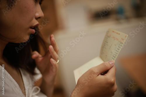 Fototapeta 貯金通帳を見て悩む女性 obraz